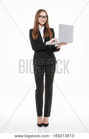 Full length portrait of a beautiful young woman in formalwear working on laptop and smiling isolated on white background