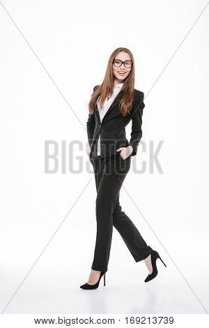 Full length portrait of a confident young business woman in formalwear and eyeglasses walking and holding hands in pockets isolated on white