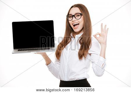 Cheerful young businesswoman holding laptop with blank screen and showing okay gesture over white background