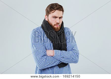 Sad ill bearded man in scarf with thermometer in his mouth