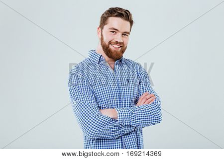 Happy handsome young man standing with arms crossed