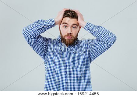 Worried bearded young man standing with hands on head