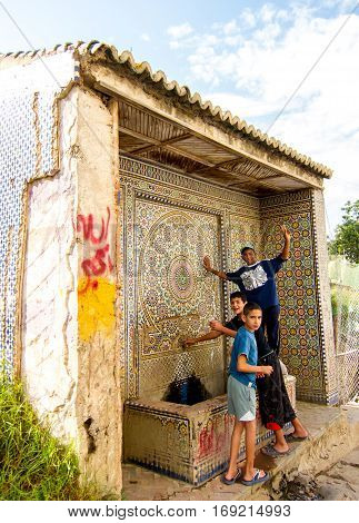 Larache, Morocco - September 16, 2010: Group of children posing for camera at a water fountain on the way to port
