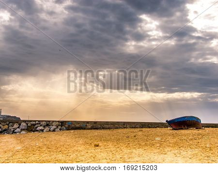 Blue boat on the beach, dramatic weather