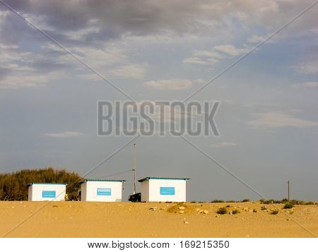 Three huts on a beach, dramatic weather in Larache, Morocco
