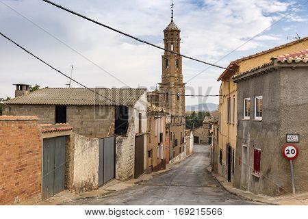 a street in Ferreruela de Huerva town and the Virgen de la Asuncion church, province of Teruel, Aragon, Spain