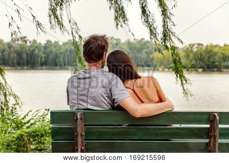 Couple in love - Two young lovers sitting together on a park bench looking at view of romantic lake. Beijing Summer Palace. Healthy happy relationship concept.