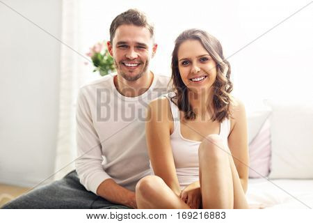 Picture showing happy couple sitting on the bed in nightwear
