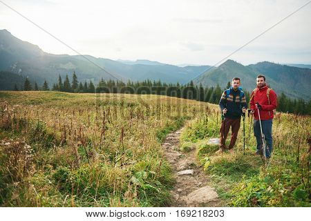 Portrait of two young men wearing backpacks and carrying trekking poles standing on a trail while hiking in the hills
