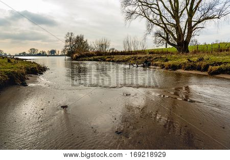 On the banks of a tributary of a large river in the Netherlands.