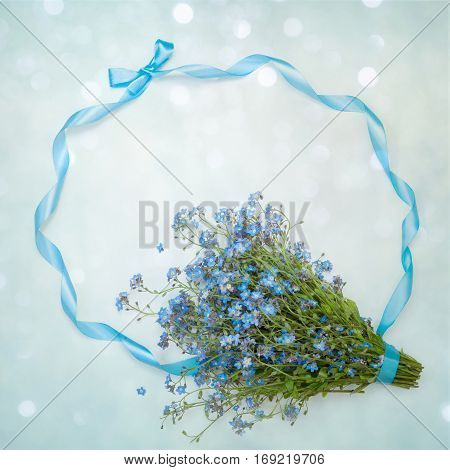 Beautiful decorative floral arrangement with wild flowers forget-me-nots and ribbons on a delicate blue background. Flat lay. Greeting Card for Valentines Day Mothers Day Birthday wedding.