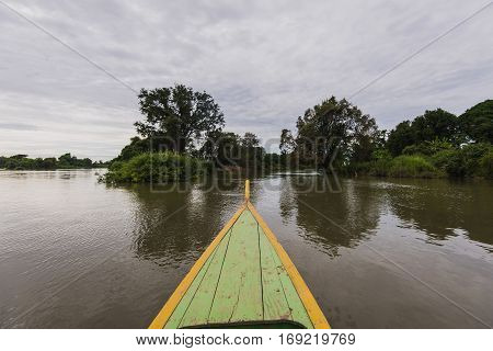 The front of an old Vietnamese Boat on a lake and trees.