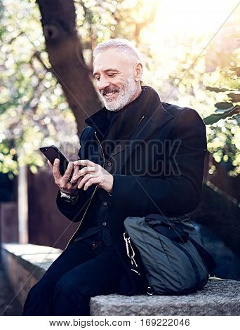 Portrait of smiling and happy middle age businessman using modern smartphone while spending time in city park at sunny day.Vertical, blurred background