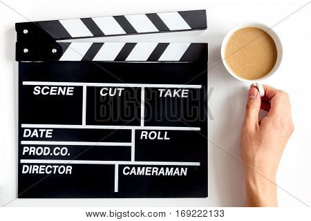 Screenwriter desktop with movie clapper board on white background top view