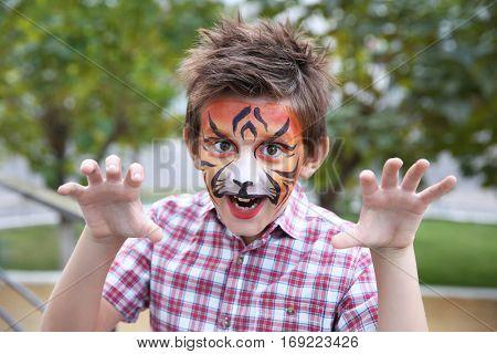 Cute little boy with aqua makeup of tiger muzzle