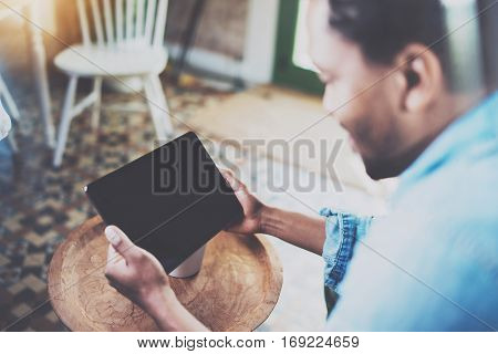 Attractive bearded African man using laptop while relaxing on armchair in modern office.Concept of young business people working at home.Blurred background.Selective focus on hands with tablet.Flares