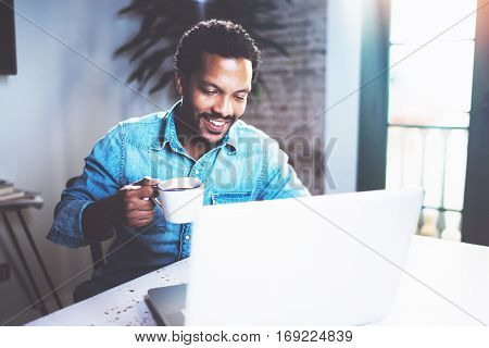 Smiling bearded African man using laptop home while drinking cup black coffee at the wooden table.Concept of young people working on mobile devices.Blurred window background