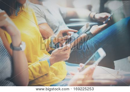 Group of young hipsters sitting on sofa holding en hands and using digital tablet, smartphone.Coworking team concept.Horizontal, blurred background