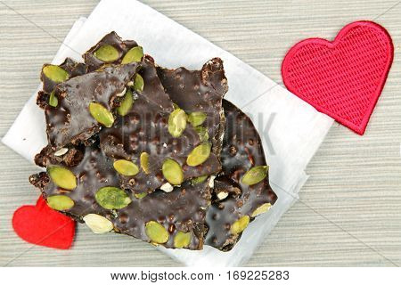 Top down view of a stack of dark chocolate bark with pine nuts and cranberries