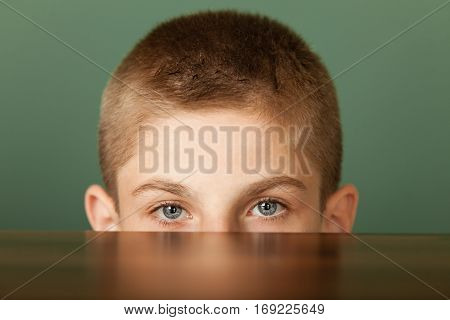 Boy Peeping Out Table Surface