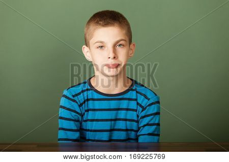 Portrait of upset sulking young boy showing his displeasure by sitting at desk against green chalkboard background poster