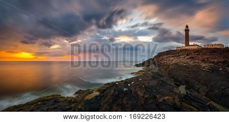 Lighthouse on cliffs of Ardnamurchan Point in colorful sunset Highlands Scotland