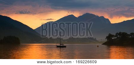 Sailing boat in colorful sunset reflections on Loch Leven panorama from Glencoe Scotland