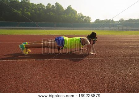 young woman runner practice push up on stadium track