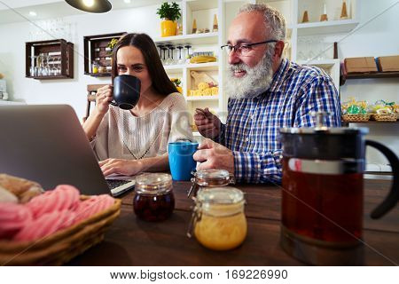 Low angle of domestic meeting in the kitchen, couple looking at the screen. They are friendly to each other. Teapot with hot tea and cups on a table black tea flavored jams, tea, biscuits