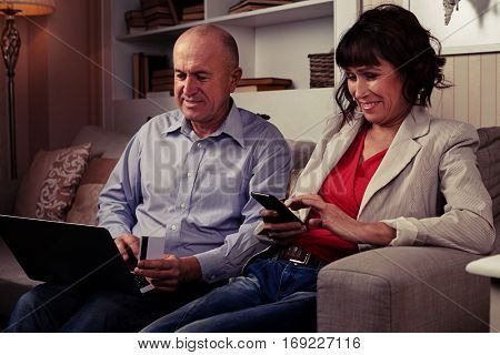 A mid side shot of an elderly pair on the couch, smiling and looking at gadgets. Man in blue shirt holding a card and female in red blouse and light stripped blazer
