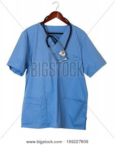 Blue medical scrubs uniform shirt hanging on a hanger with stethoscope and isolated against white background