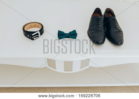 Trendy men's strap bow tie and shoes. Accesories, close-up. Set groom bow ties, shoes on white background