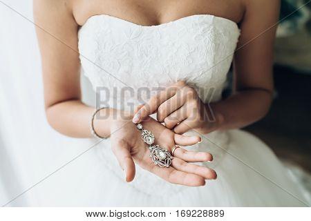 Elegant bride hanging silver earrings. Tender bridal hands with wedding accessories. Morning bridal preparation. Fine art details.