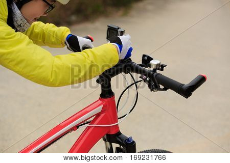 cyclist setting active camera before riding mountain bike on forest trail