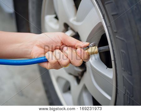 driver checking air pressure and filling air in the tires close up