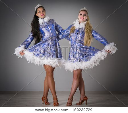 four girls dressed as Snow Maiden celebrate Christmas on a gray background