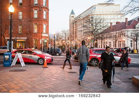 Washington DC, USA - December 29, 2016: People crossing street on Pennsylvania avenue in downtown at dusk by national mall