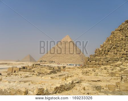 Many tour buses and people by great pyramids in Giza