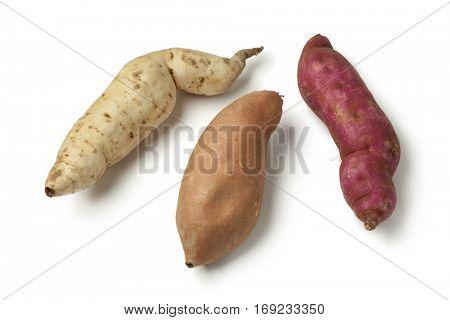Purple, white and orange sweet potatoes on white background