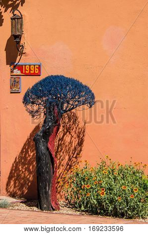 Las Cruces, United States - July 27, 2015: Blue decorative tree by adobe house in New Mexico