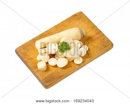 sliced parsley root on wooden cutting board