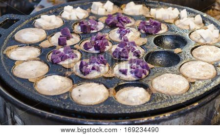 Kanom Krok Sweet and savory grilled coconut-rice hotcakes. Asian street food dessert Thai street market Bangkok Thailand