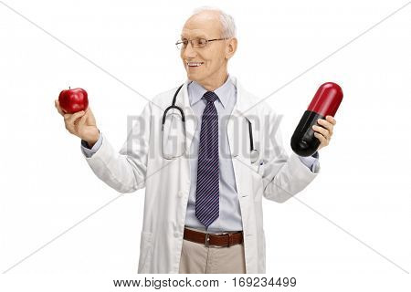 Tempted mature doctor holding an apple and a big pill isolated on white background