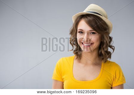 young woman wearing yellow shirt hat and jeans shorts  make faces over grey background