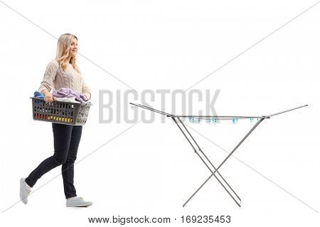 Full length portrait of a woman holding a laundry basket full of clothes and walking towards a clothing rack dryer isolated on white background