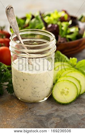 Homemade ranch dressing in a mason jar with fresh vegetables