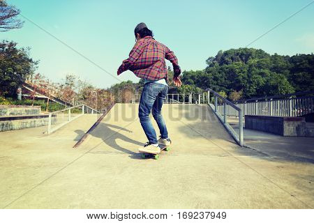 closeup of one young woman skateboarder skateboarding at skatepark