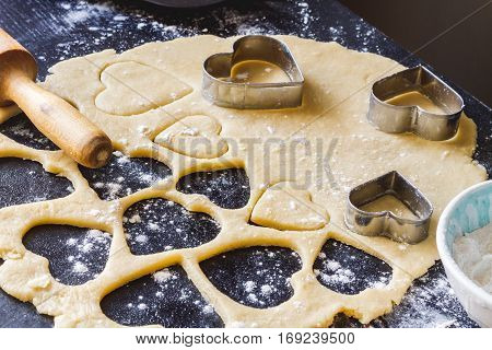 cooking homemade cookies with hands on dark background.