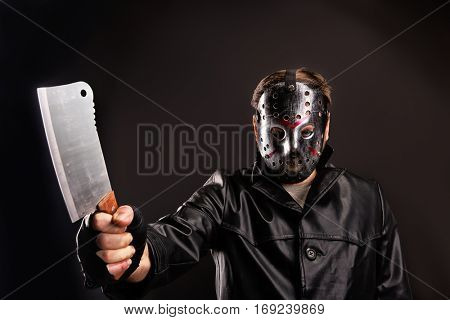 Murderer in hockey mask with meat cleaver in hand