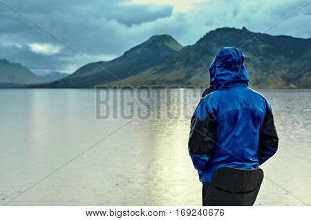 man on the Lake coast with mountain reflection at the rainy day, Iceland